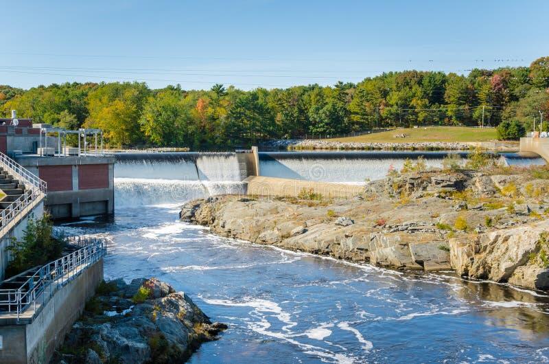 Hydroelektrisch flechten Sie entlang einem Fluss und einem blauen Himmel lizenzfreies stockbild