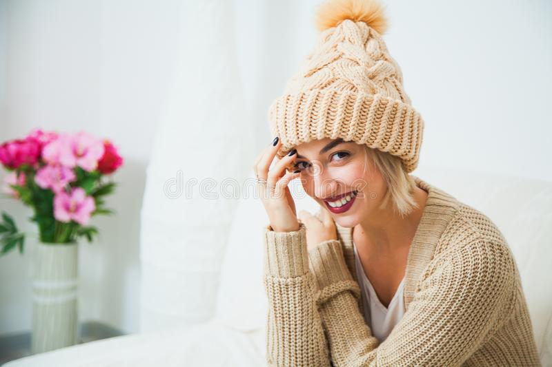 Hygge, comfort and home concept. Young woman in warm beige hand knitted hat at home. Pretty lady in big wool cap, smiling happily royalty free stock photos