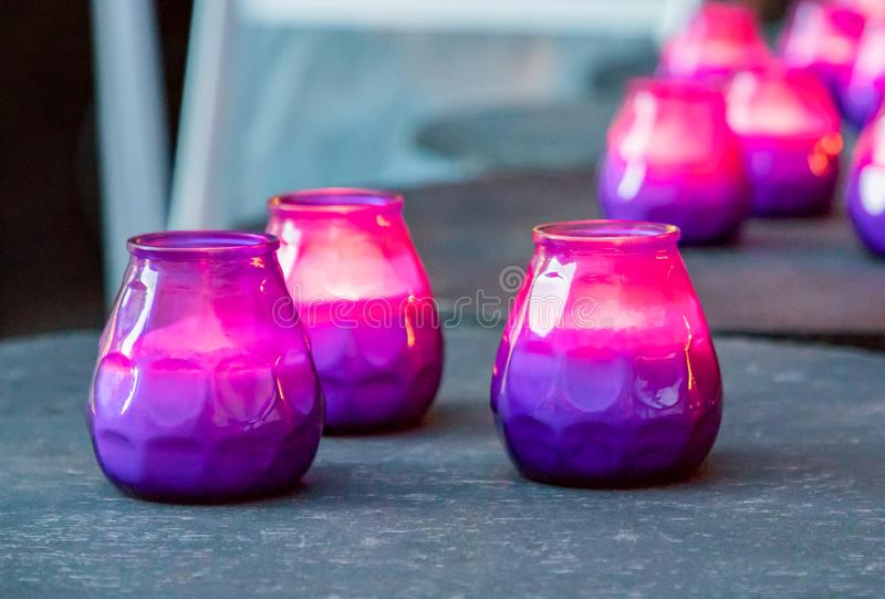 Hygge concept. Burning purple and pink candles on the table. Hygge concept. Bright burning purple and pink candles on the dark table royalty free stock photography