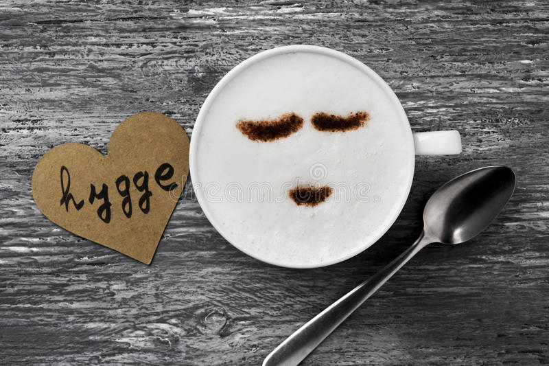 Hygge, danish word for comfort or enjoy. High-angle shot of a cup of cappuccino with a happy face drawn with cocoa powder and a signboard with the text hygge, a royalty free stock photography