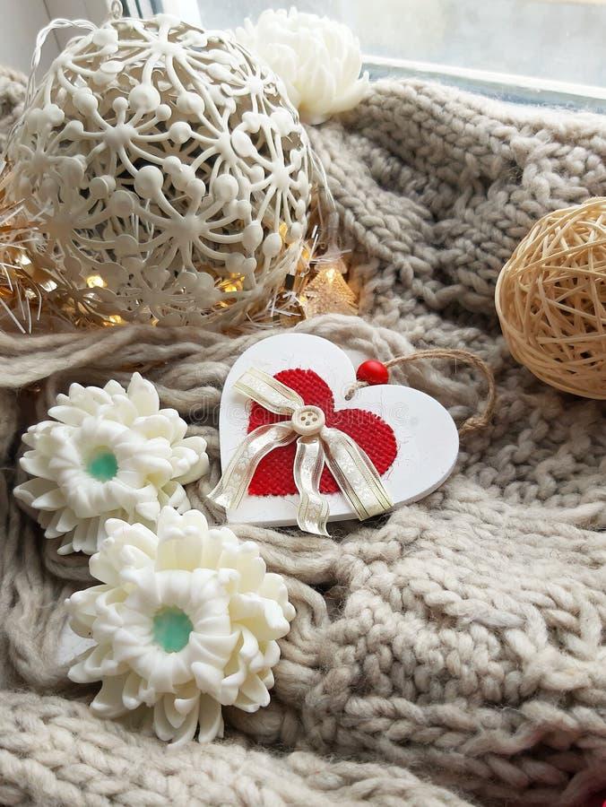 Hygge feriesammansättning Trähjärta med textildetaljer, handgjord tvål, dekorativa bollar, stucken halsduk på fönsterbräda arkivfoto