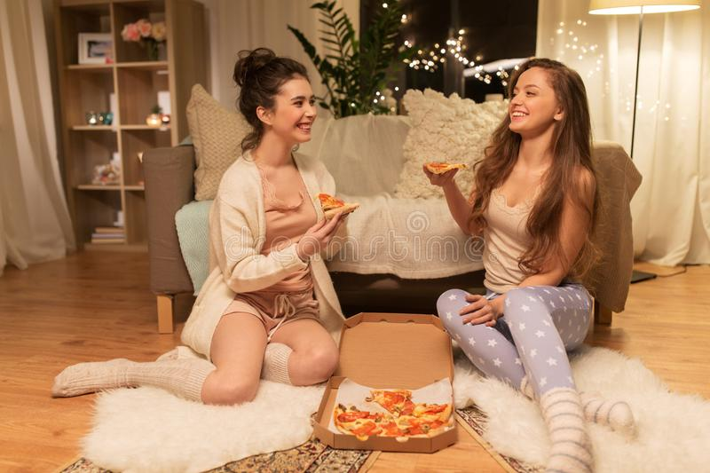 Happy female friends with pizza at home stock photo