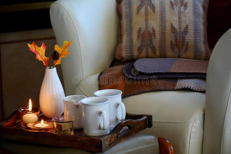 Hygge Danish home comfort. Hygge home comfort with soft leather bucket chair, candles, blanket and tea. Horizontal format in natural light royalty free stock photo