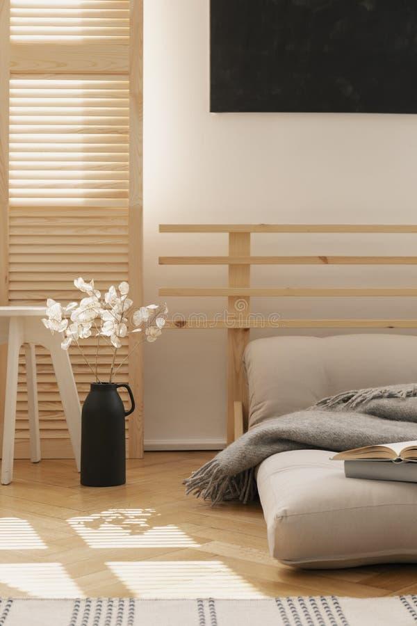 Hygge inspirerade sovrummet med den scandinavian futonen som en säng och vita blommor i den svarta vasen, verkligt foto med kopie arkivfoto