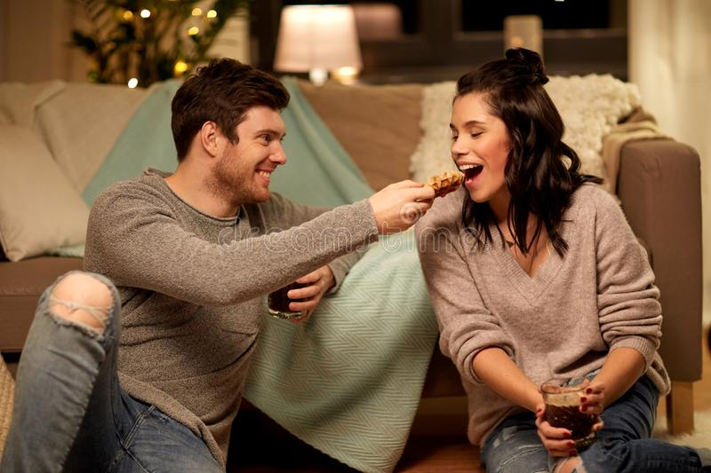 Happy couple eating waffles with cacao at home. Hygge, leisure and people concept - happy couple drinking cacao and eating waffles at home royalty free stock photography