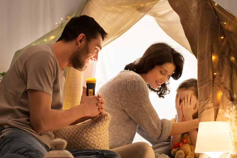 Father telling scary stories to his daughter stock photography