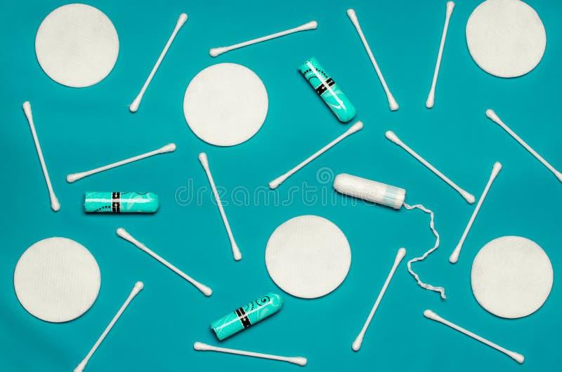 Hygiëneproducten: de ronde witte katoenen stootkussens en de katoenen zwabbers zijn op gekleurde achtergrond stock afbeelding