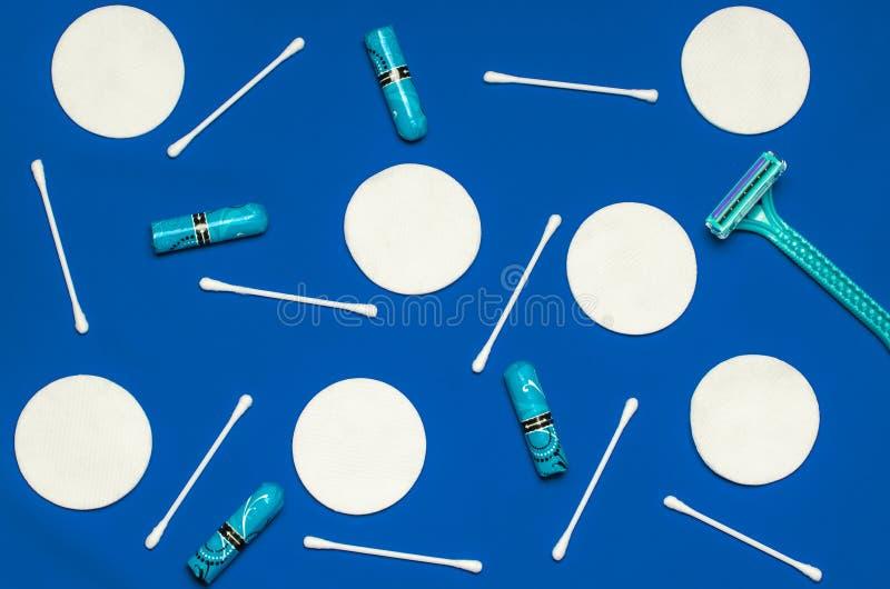 Hygiëneproducten: de ronde witte katoenen stootkussens en de katoenen zwabbers zijn op gekleurde achtergrond stock fotografie