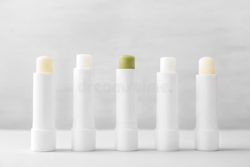 Hygiënische lippenstiften op lijst stock afbeeldingen