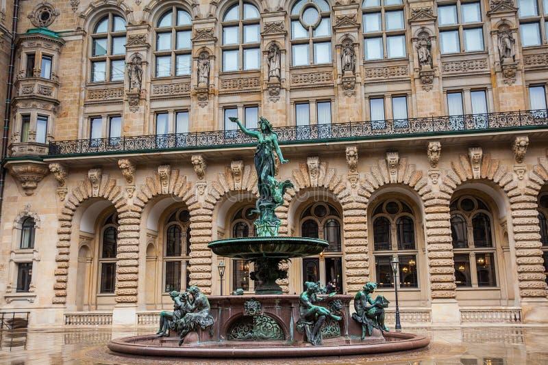 Hygieia springbrunn i borggården av det Hamburg stadshuset i en kall regnig tidig vårdag royaltyfri foto