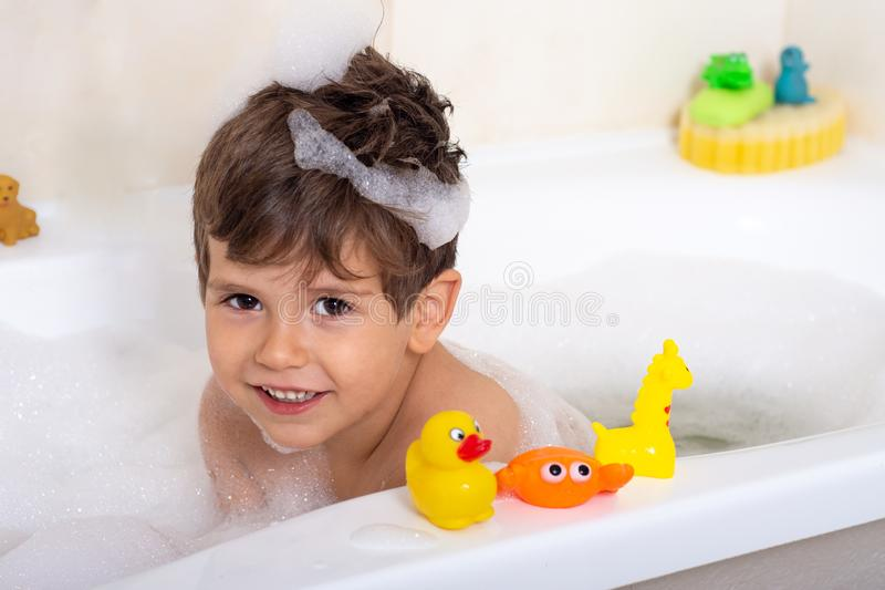 Hygiene for infant and baby. Child playing with soap foam in home bathroom. Rubber duck in foam bath stock photography