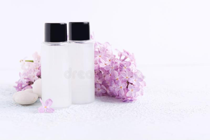Hygiene products for bath or shower. Spa concept. Cosmetic shampoo or shower gel. Natural lilac and stones. Mockup. Selective focus. Copy space royalty free stock images