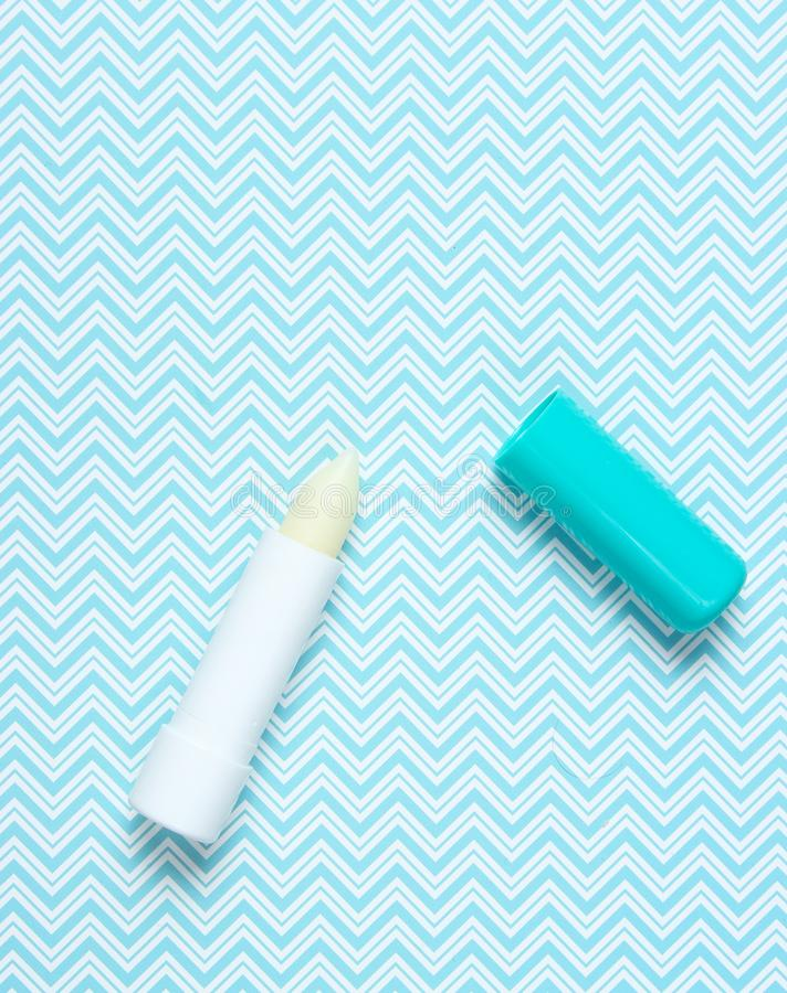 Hygienisk läppstift på en idérik blå bakgrund, minimalism, bästa sikt royaltyfria bilder
