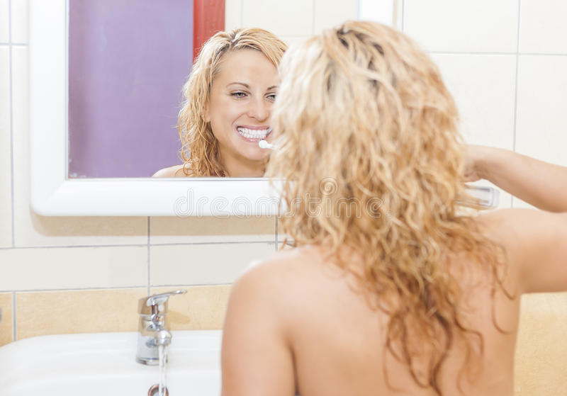 Hygieniskt tand- tillvägagångssätt Caucasian kvinna med den moderna elektriska tandborsten i badrum arkivbild
