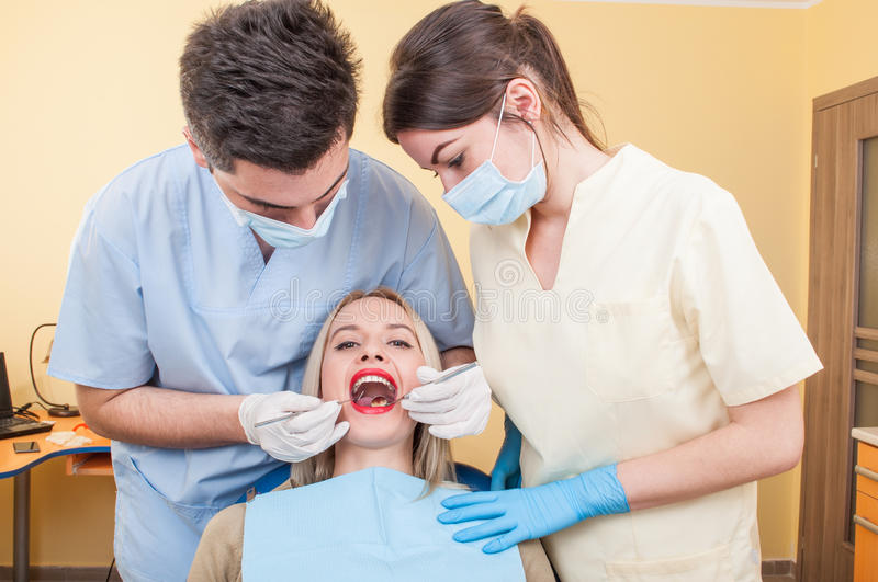 Hygienist working. With assistant on a beautiful women patient with perfect teeth royalty free stock photos