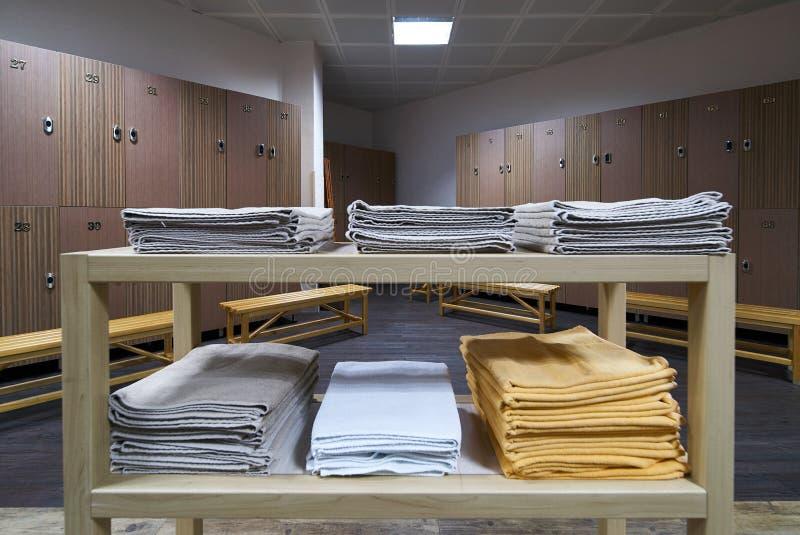 Hylla för rena handdukar i en omklädningsrum med låsbara skåp med träbänkar i luxur royaltyfri bild