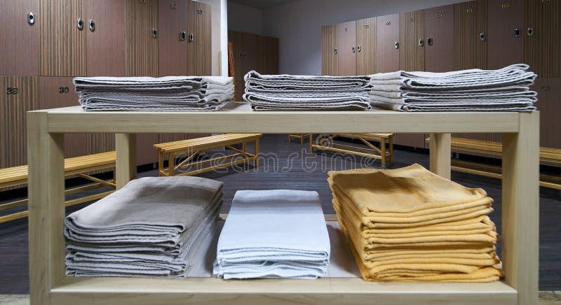 Hylla för rena handdukar i en omklädningsrum med låsbara skåp med träbänkar i luxur royaltyfria foton