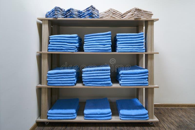 Hylla med staplade blåa rena badlakan royaltyfria foton