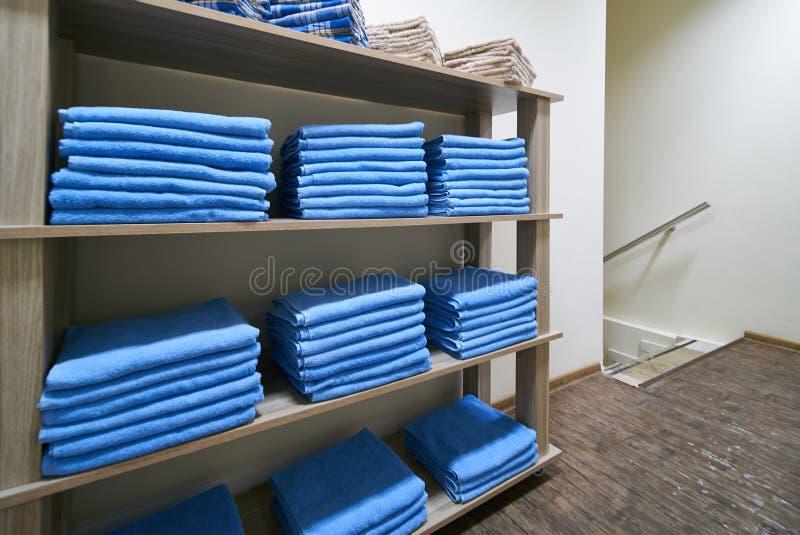 Hylla med staplade blåa rena badlakan royaltyfri fotografi