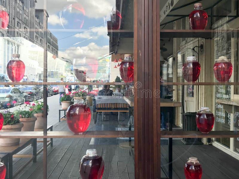Hyllor i gatan med glödande ljusa cans för stort rött genomskinligt exponeringsglas, behållare, flaskor med smaklig söt fruktsaft royaltyfria foton