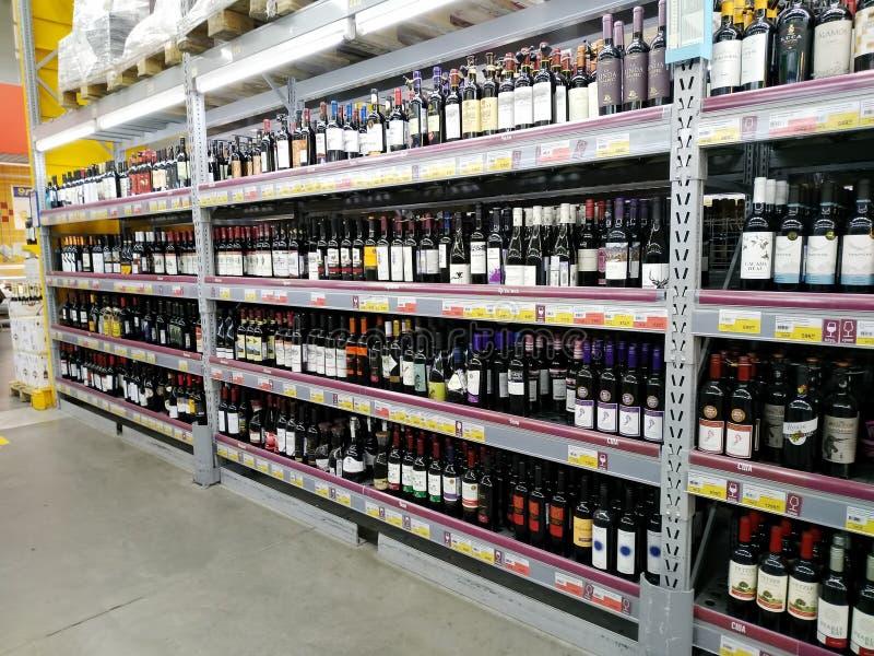 Hyllor med flaskor av olika slag av rött vin i en supermarket Lenta arkivbild