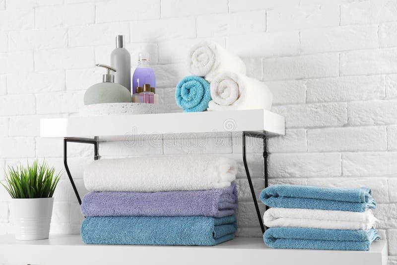 Hyllor med rena handdukar och toalettartiklar arkivfoto