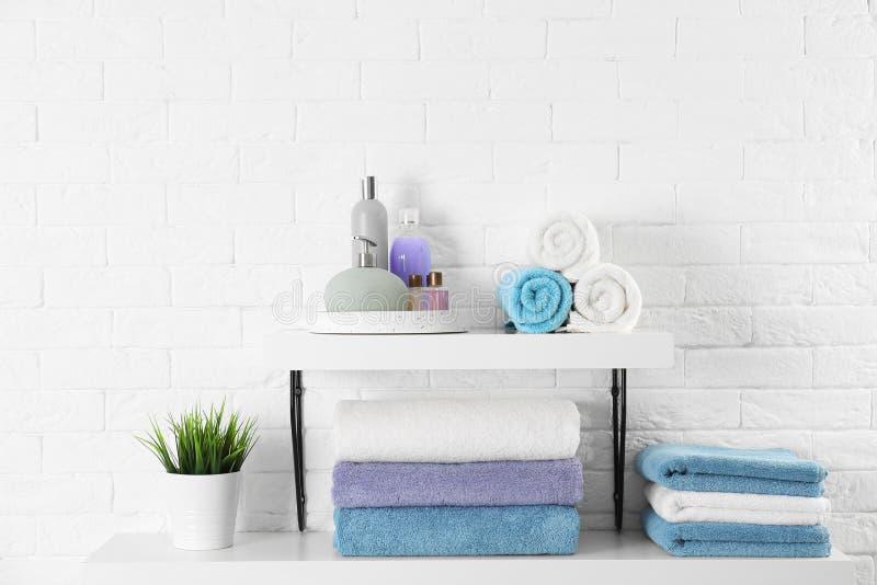 Hyllor med rena handdukar och toalettartiklar arkivbilder