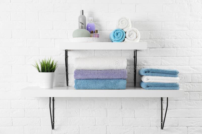Hyllor med rena handdukar och toalettartiklar royaltyfria bilder