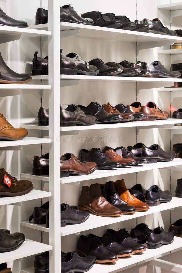 Hyllor med skor för man` s i ett lager royaltyfri bild