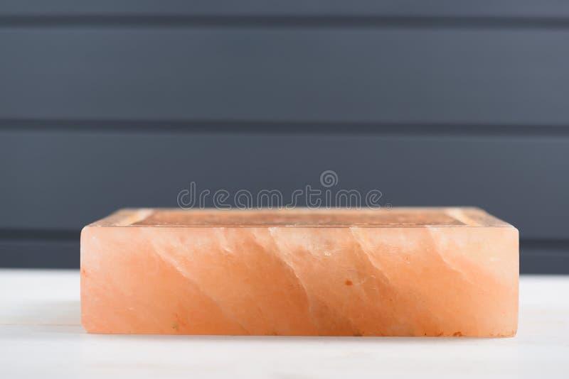 Hymalayan украшает дырочками блок соли с отказами на темной серой предпосылке si стоковое изображение rf