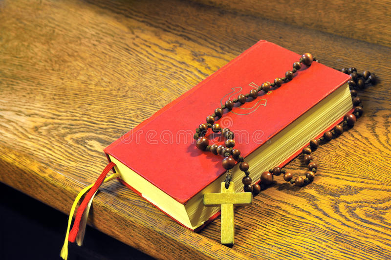 Hymnal book and wooden rosary bead stock photography