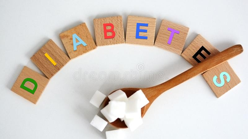 Hyperglycemia concept with white refined sugar cubes on wooden spoon and colored letters spelling the word diabetes stock photo