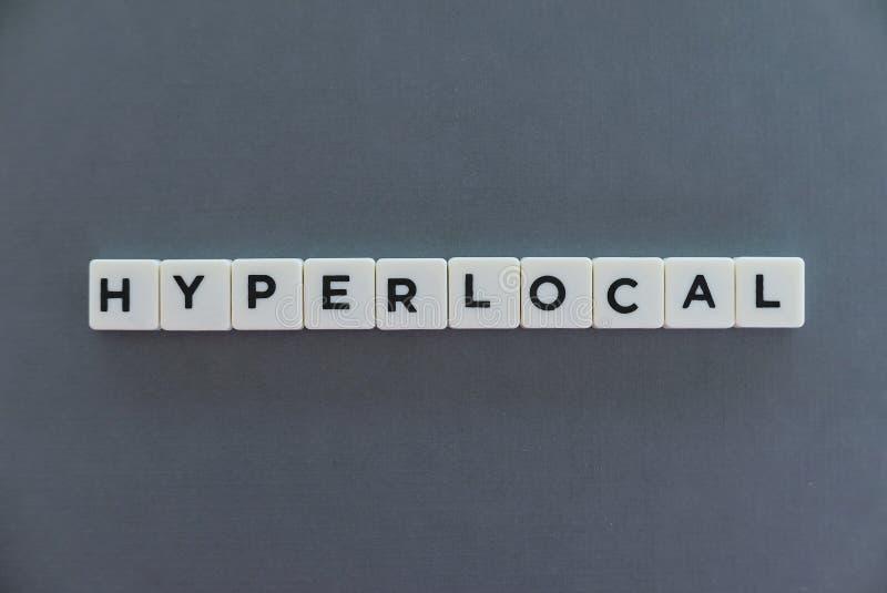 Hyperlocal ord som göras av fyrkantigt bokstavsord på grå bakgrund arkivfoton
