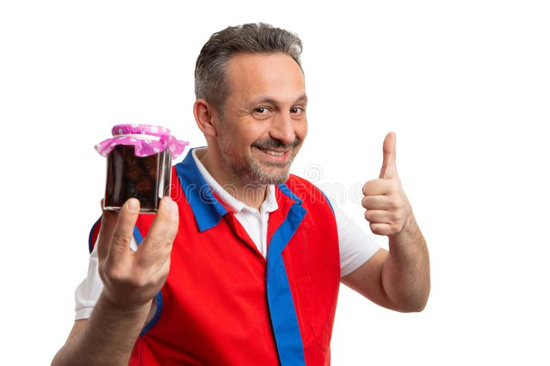 Hypermarket employee advertising jar of jam. Friendly hypermarket or supermarket male employee advertising har of jam with thumb up as like gesture isolated on stock photos