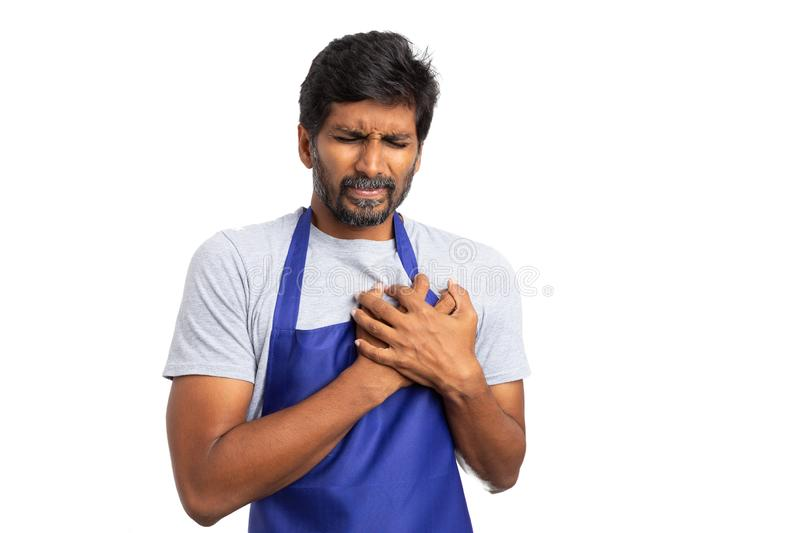 Hypermarket employee with heart pain. Stressed hypermarket or supermarket indian employee touching heart as cardiac problems concept isolated on white studio stock photo
