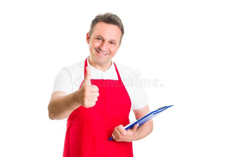 Hypermarket employee holding clipboard. Friendly hypermarket employee holding clipboard and showing thumb up stock photo