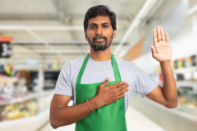 Hypermarket employee making oath. Serious trustworthy indian male hypermarket or supermarket employee making honest oath gesture with hand on heart and palm up stock photography