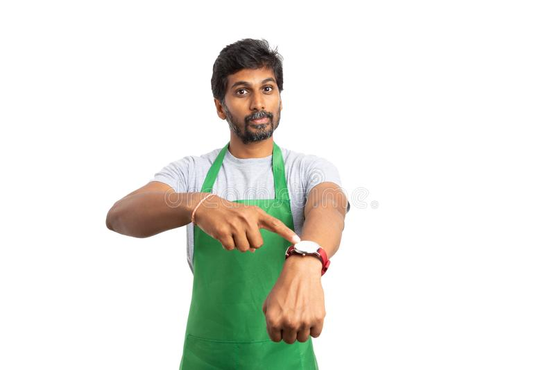 Hypermarket employee poiting watch with serious expression. Hypermarket or supermarket bossy indian employee pointing watch with index finger and having serious stock images