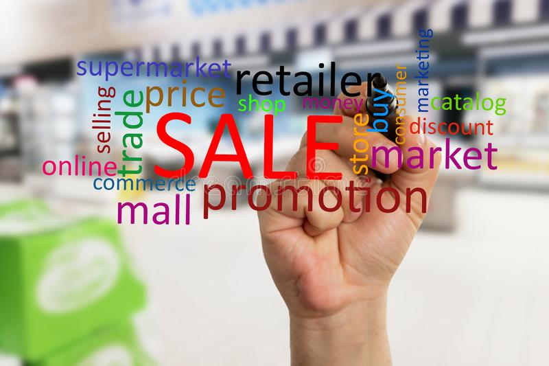 Hypermarket employee writing retailer on display. Male hypermarket or supermarket employee writing retailer text with black marker on transparent glass display royalty free stock photos