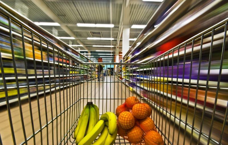 Hypermarket motion blur fruits. Motion blur inside a hypermarket w bananas and oranges stock image