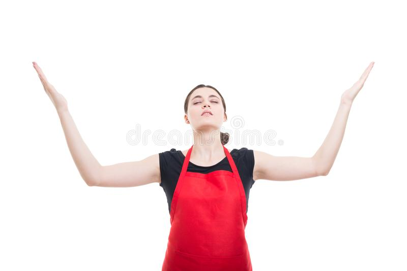 Hypermarket salesperson with uniform meditating. And rising hands up stock image