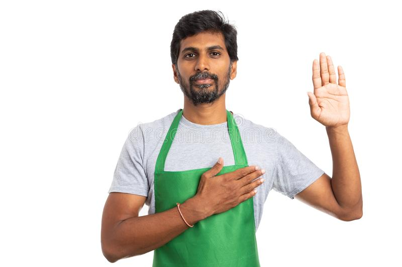 Hypermarket employee oath gesture. Hypermarket or supermarket man employee holding hand on heart and up as oath gesture expressing honesty and loyalty isolated stock image