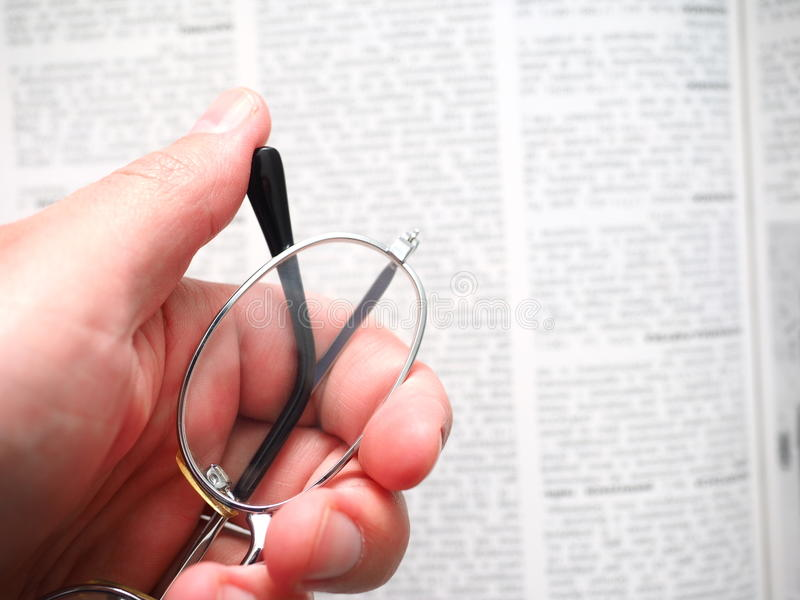 Hyperopia. Hand holding some glasses infront of an out of focus text, for concepts invloving illnesses of the eye as well as reading - retouched, selective focus royalty free stock images
