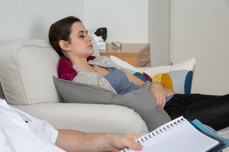 Hypnos som är erfaren på en kvinnlig patient royaltyfri bild