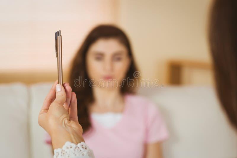 Hypnotherapist mienia pióro przed jej pacjentem fotografia stock