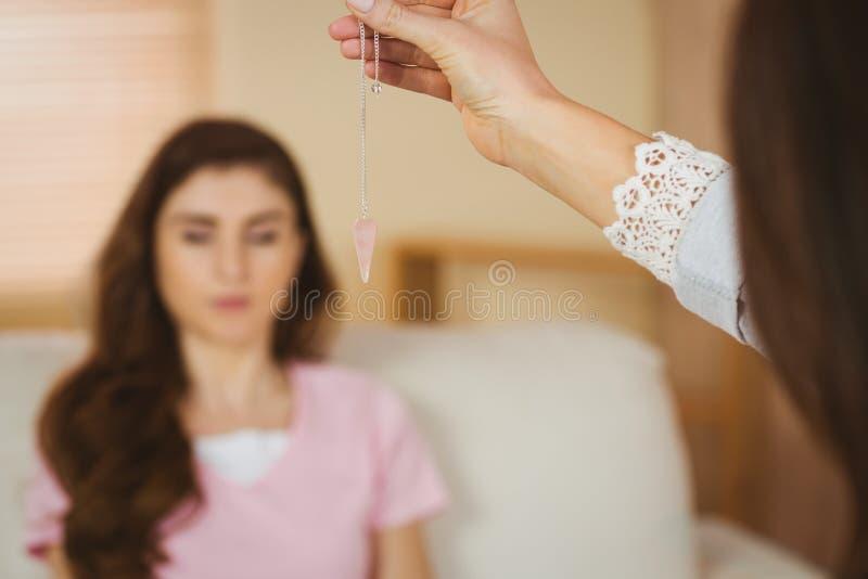 Hypnotherapist tenant le pendule avant son patient photographie stock