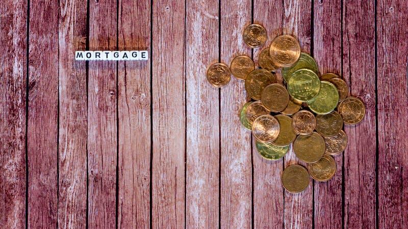 Hypothekendarlehen, Buchstabewürfel mit Münzen lizenzfreie stockfotos
