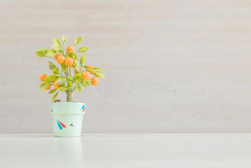 Hyr rum den konstgjorda orange växten för closeupen med orange frukt i grön kruka på det suddiga träskrivbordet och väggen textur royaltyfri bild