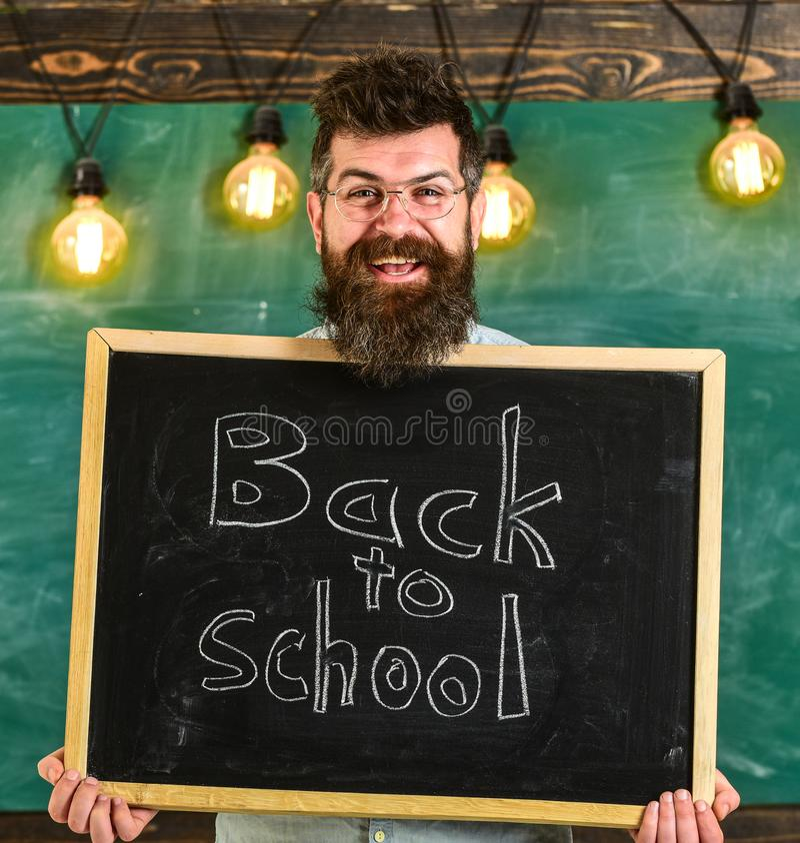 Hyra lärarebegrepp Mannen med skägget och mustaschen på lycklig framsida välkomnar kollegor, svart tavla på bakgrund royaltyfri bild