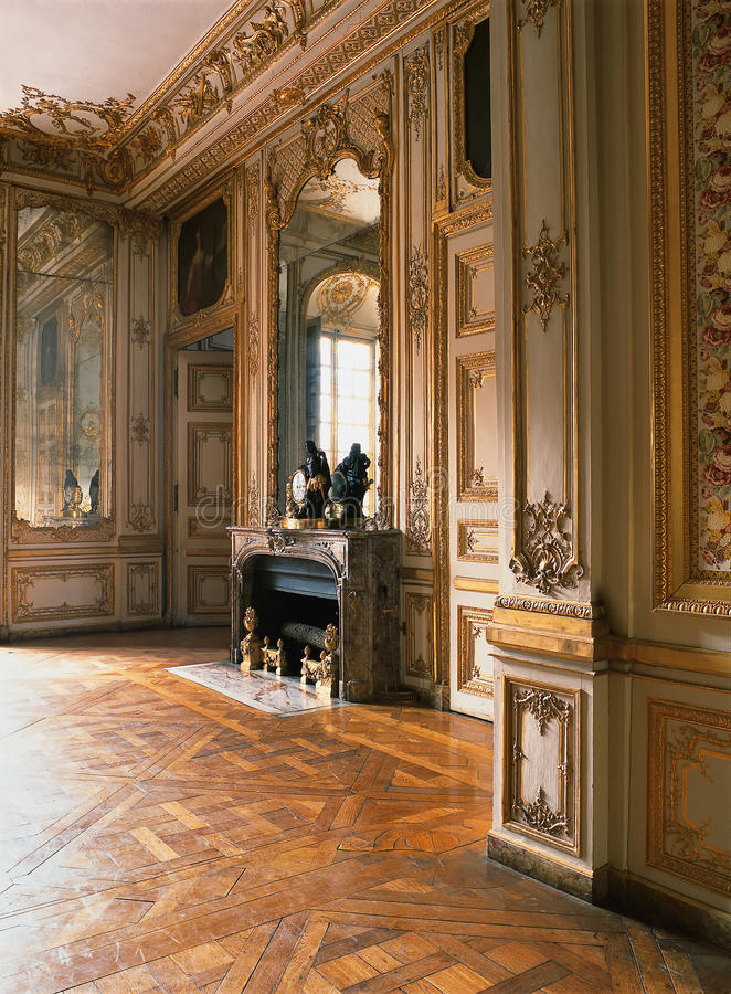 Hyra rum med den stora spegeln, det wood golvet och spisen på den Versailles slotten, Frankrike royaltyfria foton